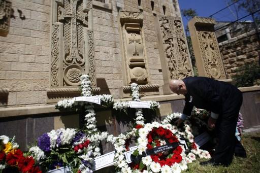 Egy örmény közösség tag virágot helyez Jeruzsálem Óvárosában található emlékműre.