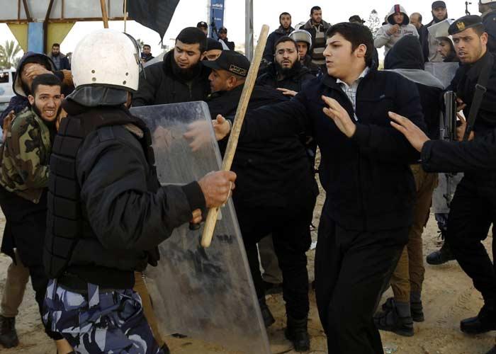 Egy Hamász-rendőr próbálja visszatartani a szalafitákat Gázában, akik a letartóztatások ellen tüntetnek.