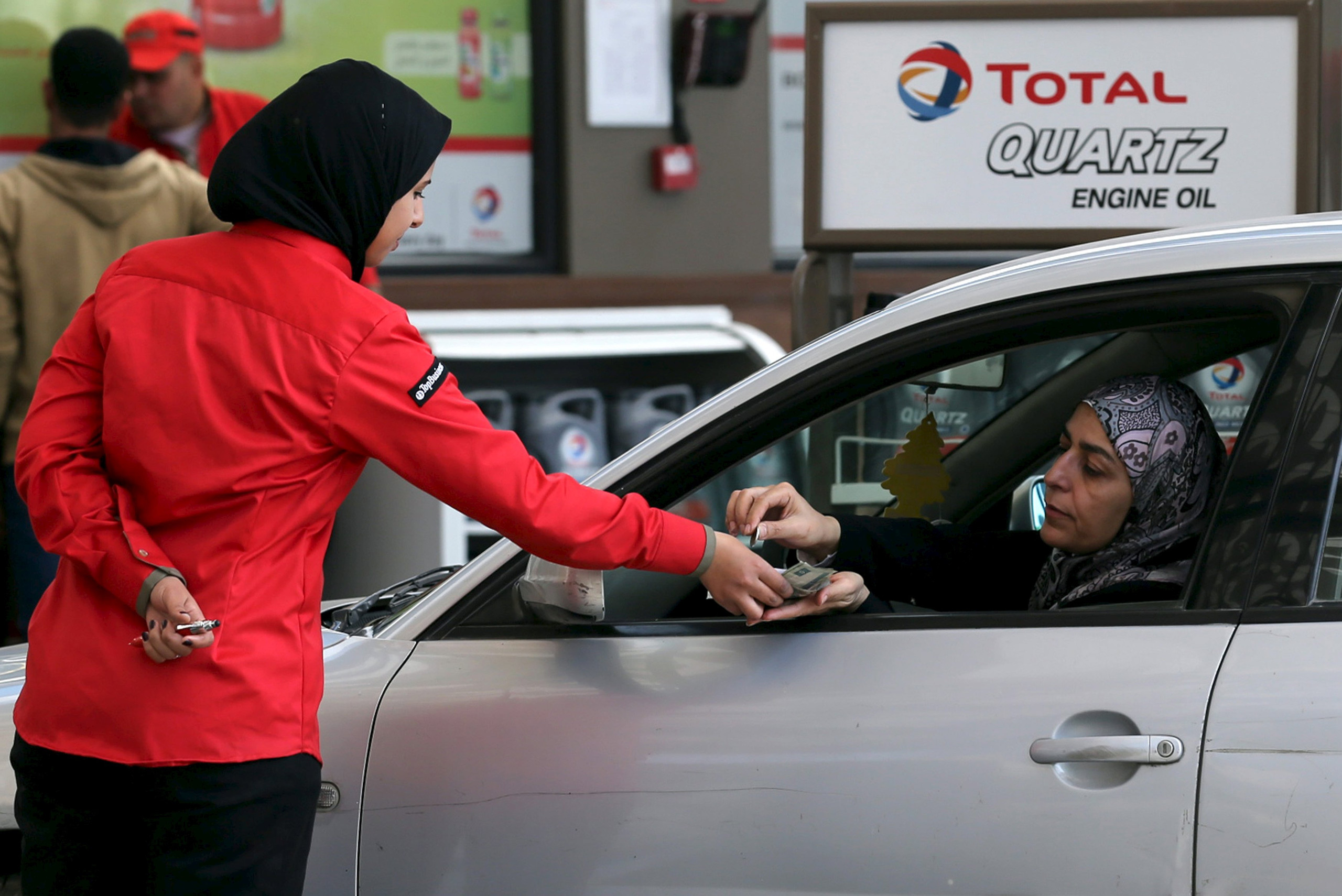 A female employee is seen at work at a petrol station in Cairo