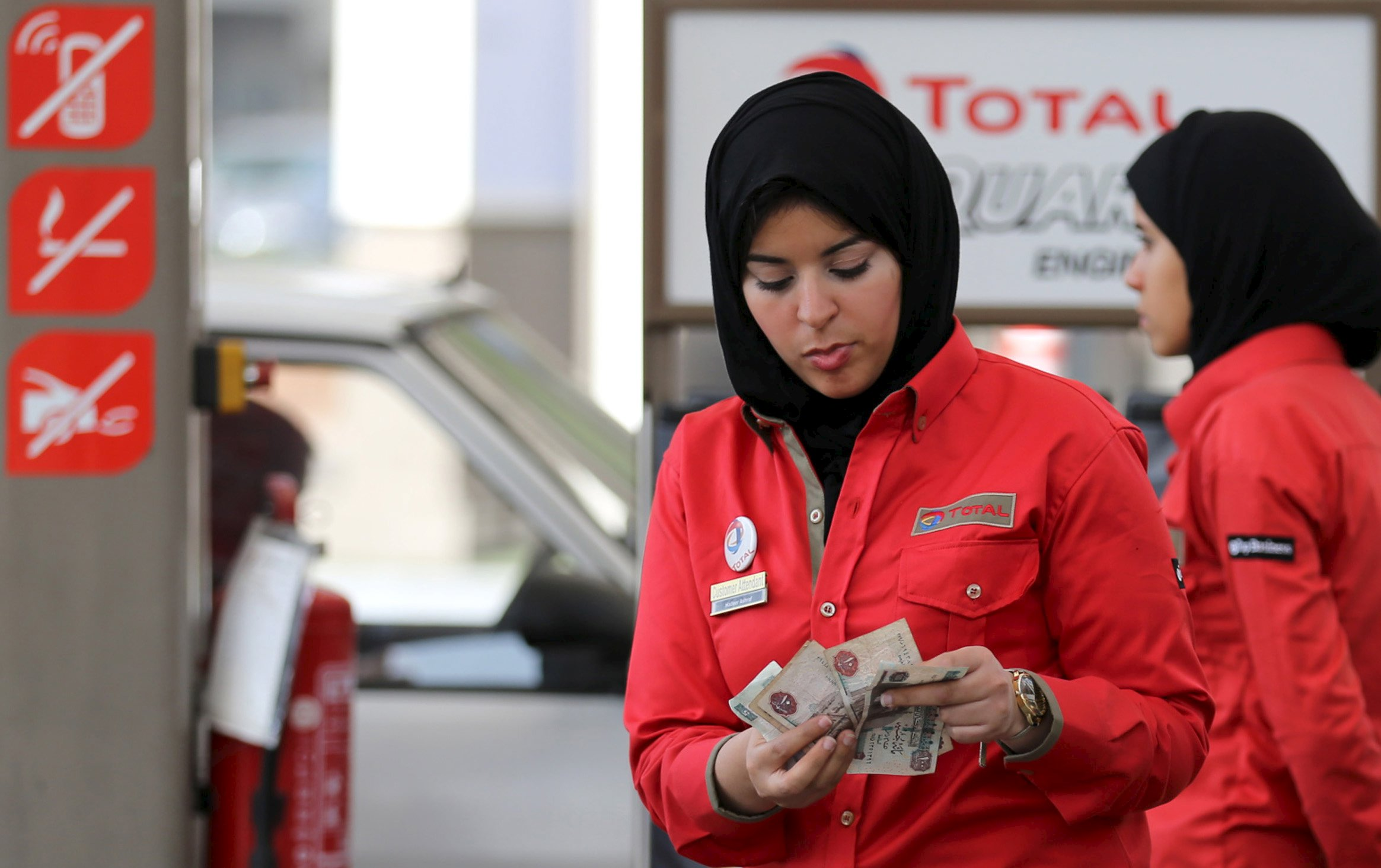 A female employee is seen as she works at a petrol station in Cairo