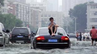 Árvízi hajós az autó tetején egy kínai nagyváros kellős közepén