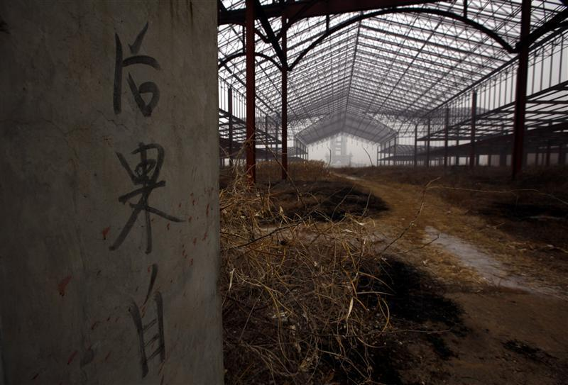 Writing on a gate is seen at an abandoned building that was to be part of 'Wonderland', on the outskirts of Beijing