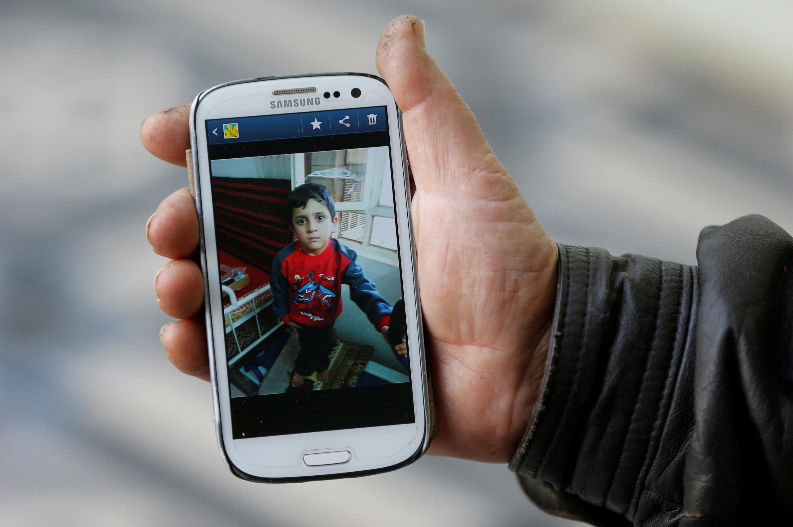 Abu Ahmed a kisfiú képeit mutatja.